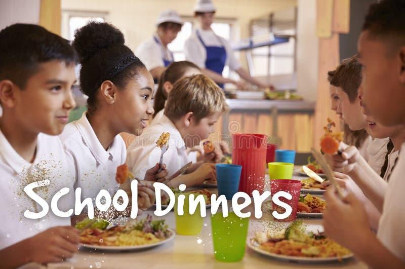 Los alumnos primarios comen cenas de la escuela en cafetería fotos de archivo libres de regalías