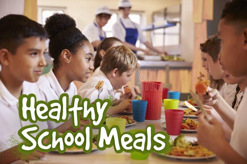 Los alumnos primarios comen comidas de escuela sanas imagen de archivo