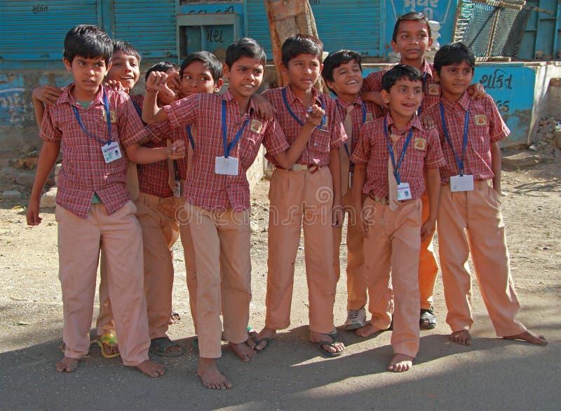 Los alumnos se vistieron en uniforme van a casa después de clases en Ahmadabad, la India foto de archivo