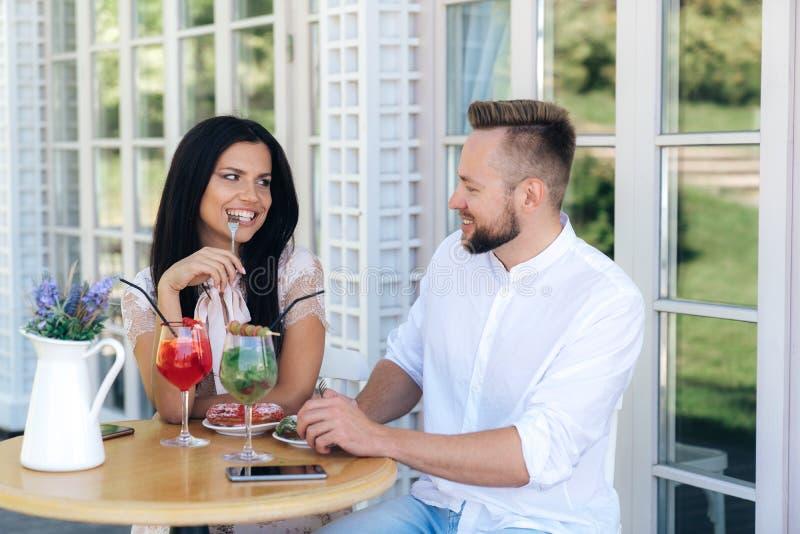 Los amantes comunican en una tabla en un café Un hombre y una mujer acaban de comenzar fechar, van a los restaurantes, caminan, p fotos de archivo