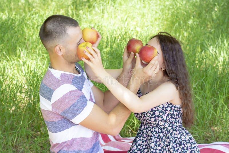 Los amantes muchacho y muchacha salpican manzanas cierran cada otras los ojos emociones Comida campestre del verano fotos de archivo