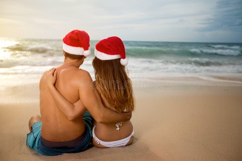 Los amantes se juntan en los sombreros de Papá Noel que se relajan en la playa arenosa imagen de archivo libre de regalías