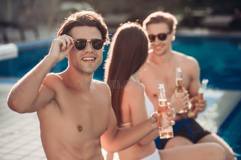 Los amigos acercan a la piscina del swimmimg fotografía de archivo libre de regalías