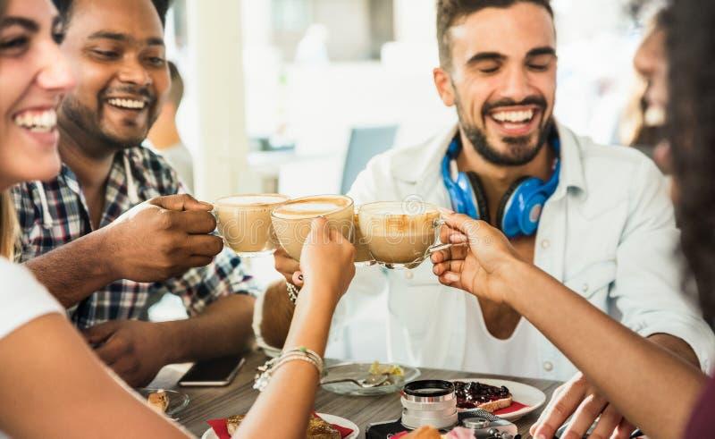 Los amigos agrupan el latte de consumición en el restaurante de la barra de café - gente t imagen de archivo