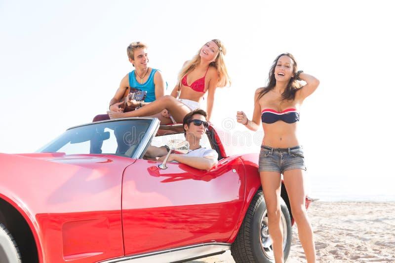 Los amigos agrupan en la playa en descapotable del coche de deportes imagenes de archivo