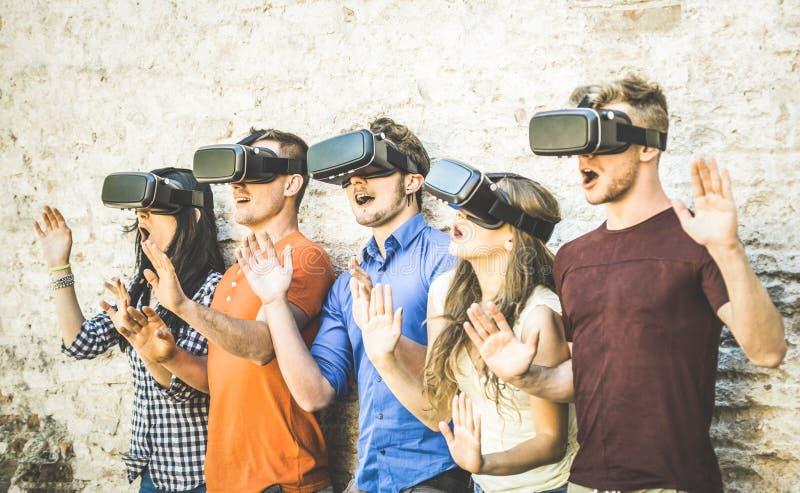 Los amigos agrupan jugar en realidad virtual de los vidrios del vr al aire libre - fotografía de archivo