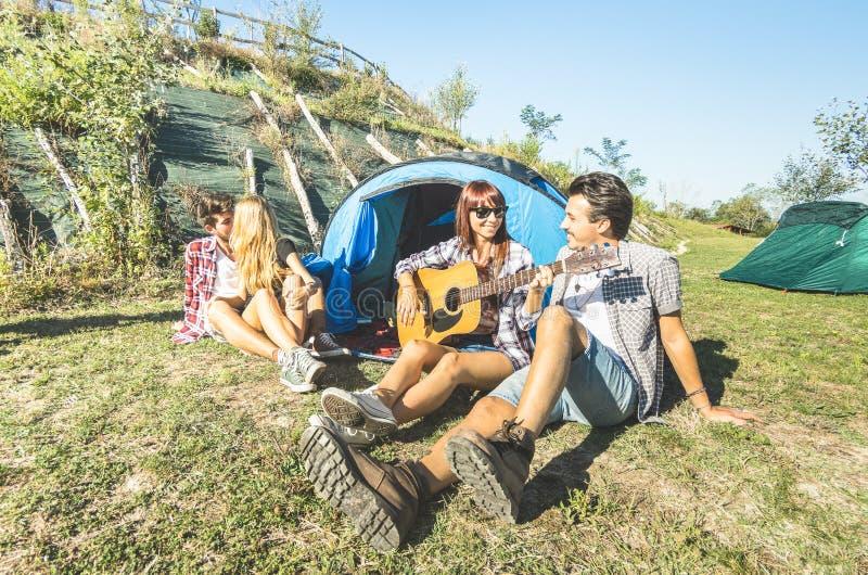 Los amigos agrupan tener animar al aire libre de la diversión en el campo de la comida campestre fotos de archivo