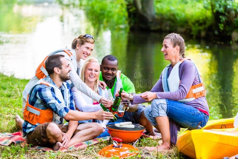 Los amigos asan a la parilla después de deportes en cerveza de consumición del bosque fotografía de archivo libre de regalías