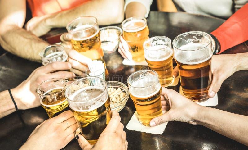 Los amigos dan la cerveza de consumición en el restaurante del pub de la cervecería - Friendsh fotos de archivo
