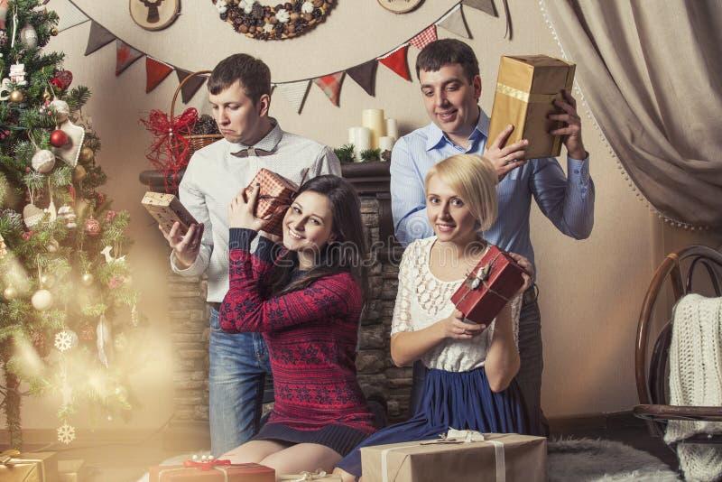 Los amigos de cuatro hombres y mujeres dan los regalos en el interi de la Navidad imagen de archivo