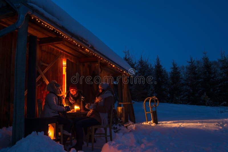 Los amigos de la cabaña del invierno de la tarde disfrutan de bebidas calientes fotografía de archivo libre de regalías