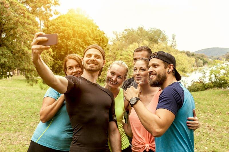 Los amigos deportivos toman un selfie del grupo durante su funcionamiento de la resistencia al aire libre foto de archivo