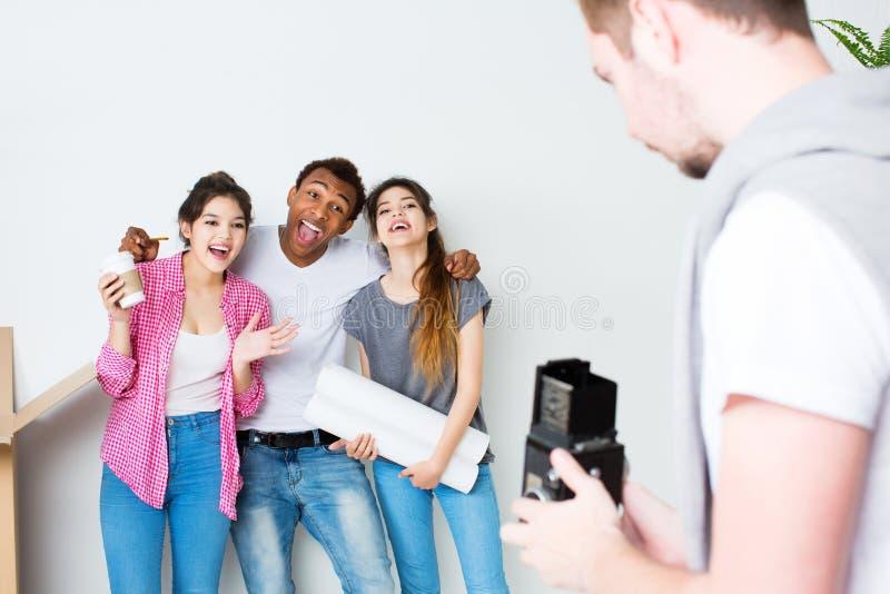 Los amigos divertidos toman la foto en una nueva casa foto de archivo libre de regalías