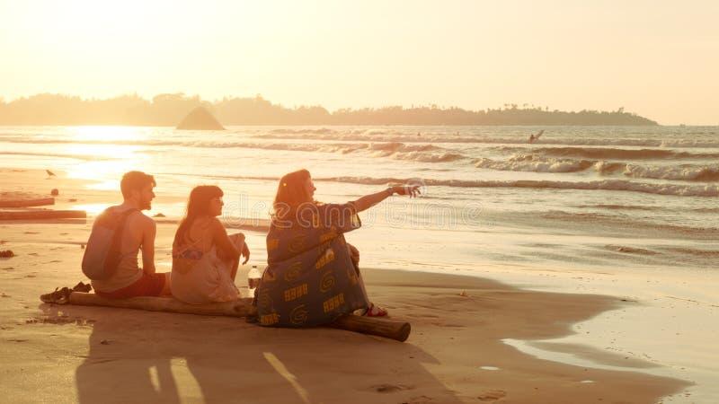 Los amigos dos mujeres jovenes y hombre se sientan en la playa tropical de la playa en la puesta del sol y miran el agua Viaje de imagenes de archivo