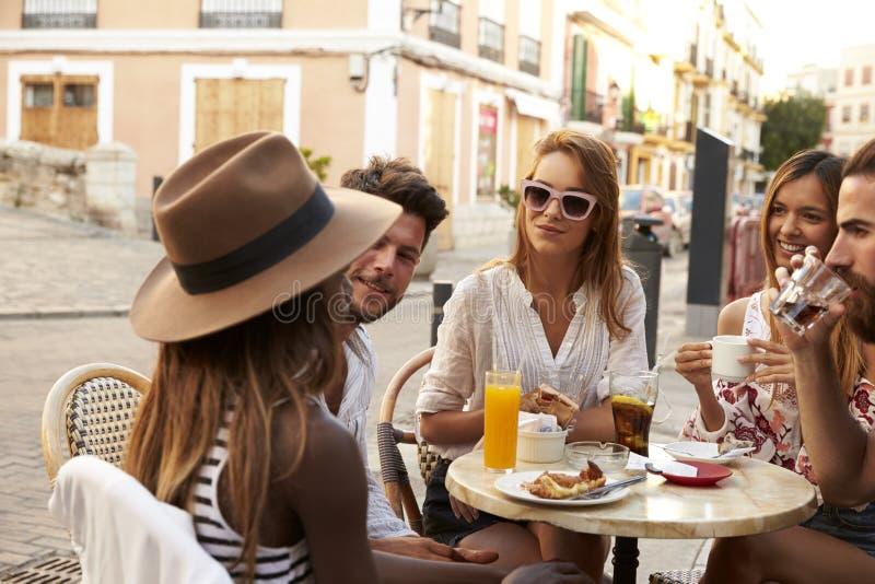 Los amigos el vacaciones sientan hablar fuera de un café en Ibiza fotos de archivo libres de regalías