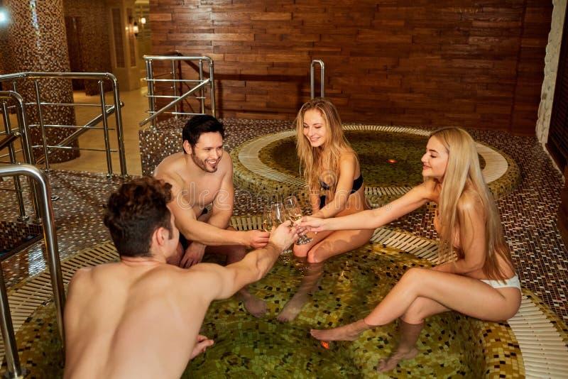 Los amigos en bañadores con el champán de cristal descansan en el bathro fotografía de archivo libre de regalías
