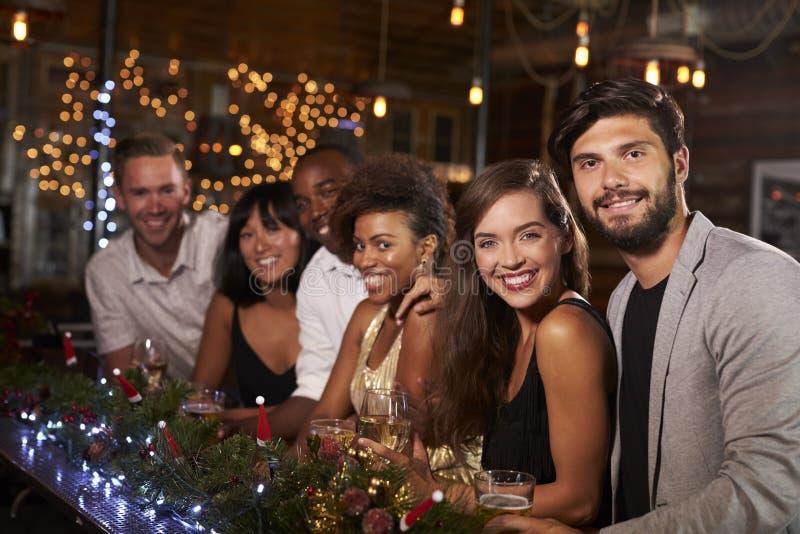 Los amigos en la barra durante una fiesta de Navidad miran a la cámara imágenes de archivo libres de regalías