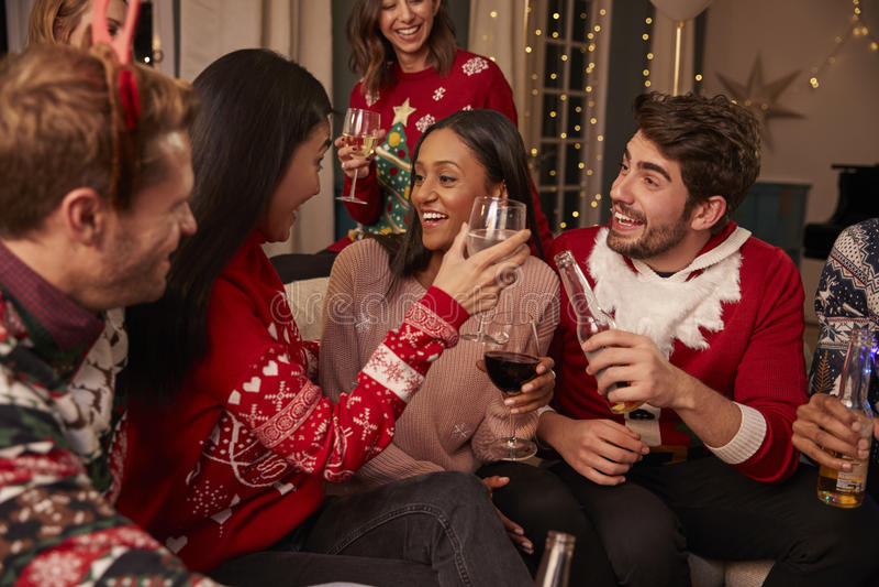 Los amigos en puentes festivos celebran en la fiesta de Navidad fotografía de archivo libre de regalías