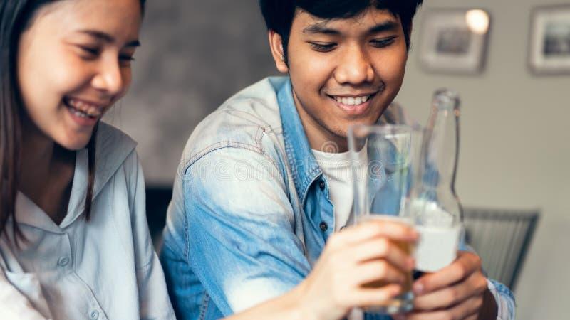 Los amigos están sonriendo, están yendo de fiesta felices en la barra y están botella que hablan y que tintinean con las bebidas imagen de archivo libre de regalías