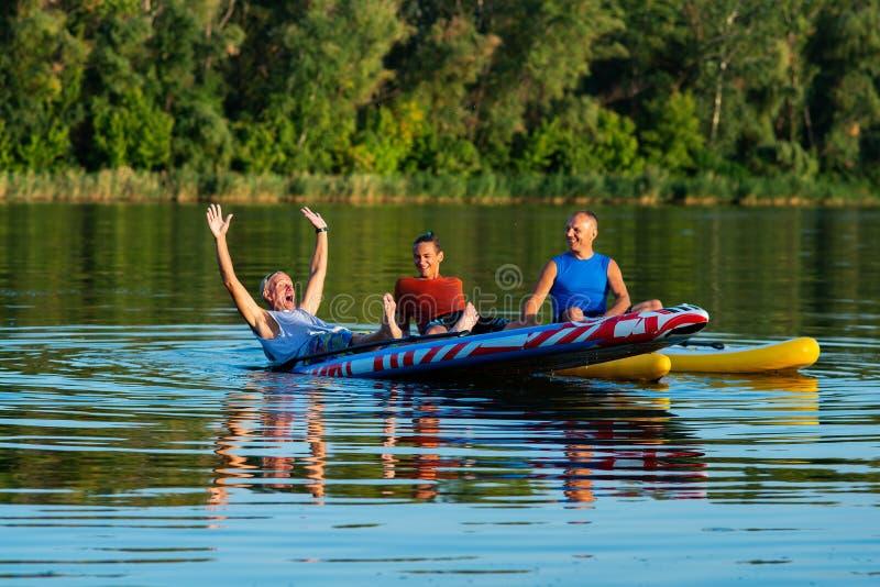 Los amigos felices, las personas que practica surf de un SORBO se relajan en el río grande durante sunse fotografía de archivo