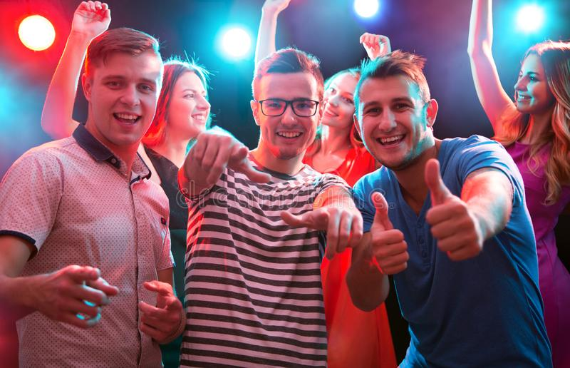 Los amigos felices que muestran la AUTORIZACIÓN firman en el club nocturno imágenes de archivo libres de regalías