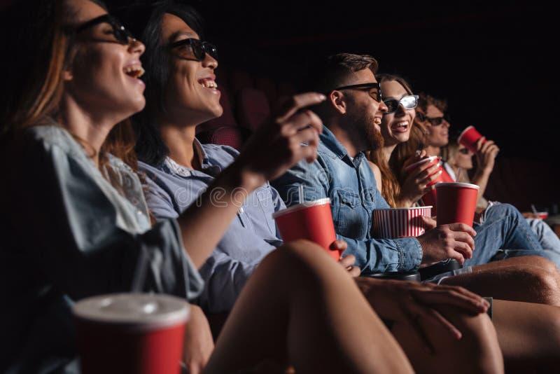 Los amigos felices que se sientan en cine miran la película el comer de las palomitas foto de archivo libre de regalías