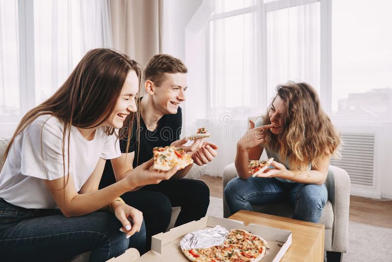 Los amigos felices se divierten que comen el partido de la pizza en casa fotografía de archivo libre de regalías