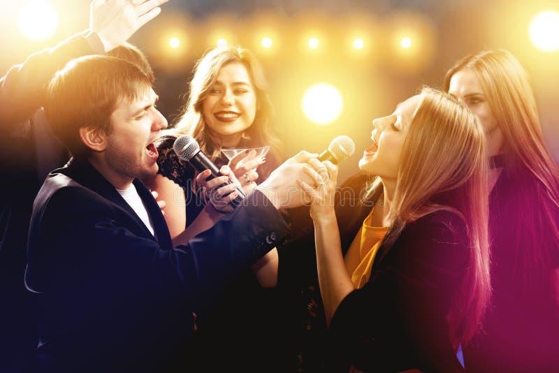 Los amigos felices son cantantes y de bailes en club de noche fotos de archivo