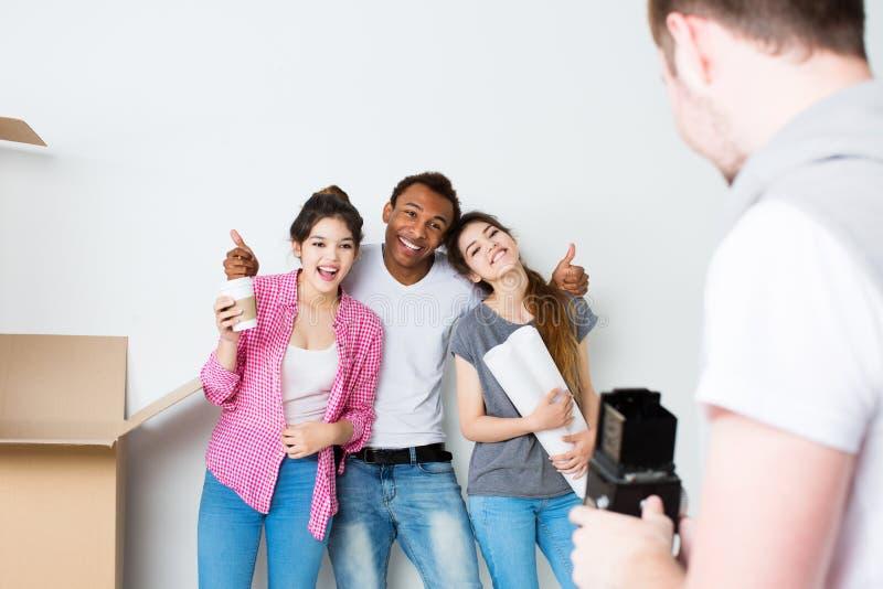Los amigos felices toman la foto en una nueva casa foto de archivo libre de regalías