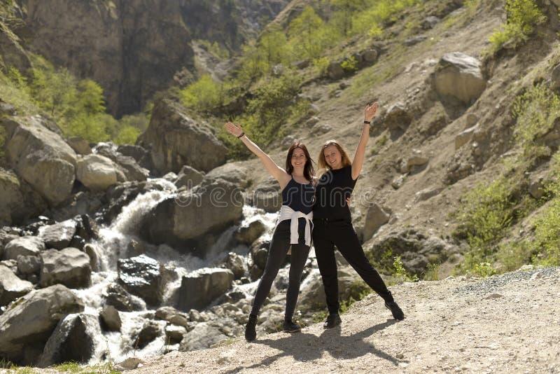 Los amigos femeninos alegres jovenes se relajan juntos en las montañas foto de archivo libre de regalías