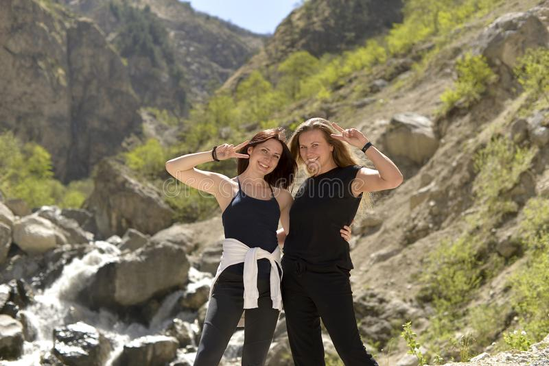 Los amigos femeninos alegres jovenes se relajan juntos en las montañas fotos de archivo libres de regalías
