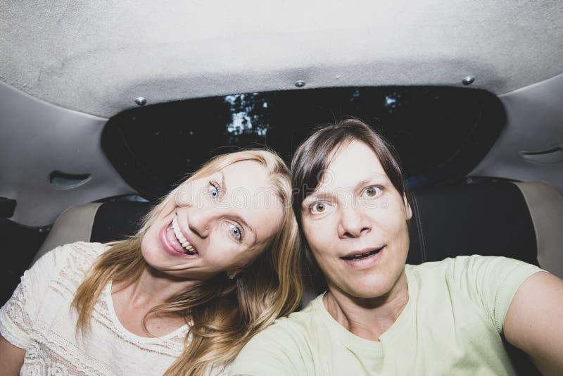 Los amigos femeninos alegres van a un partido en un taxi fotos de archivo