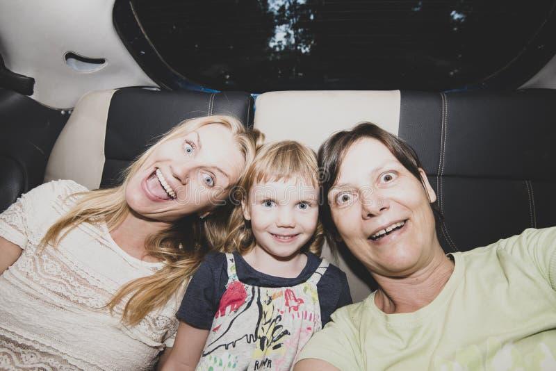 Los amigos femeninos alegres van a un partido en un taxi foto de archivo libre de regalías