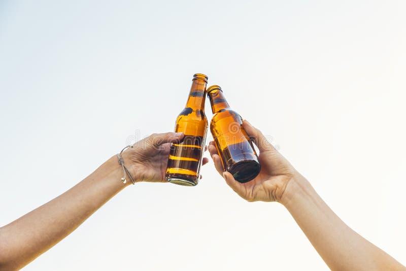 Los amigos femeninos animan las botellas que tintinean de cerveza en manos foto de archivo libre de regalías