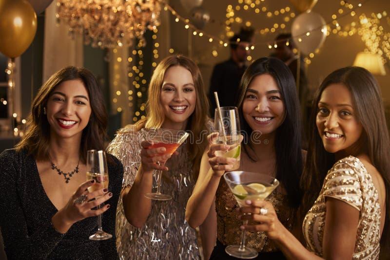Los amigos femeninos hacen la tostada mientras que celebran en el partido imagen de archivo