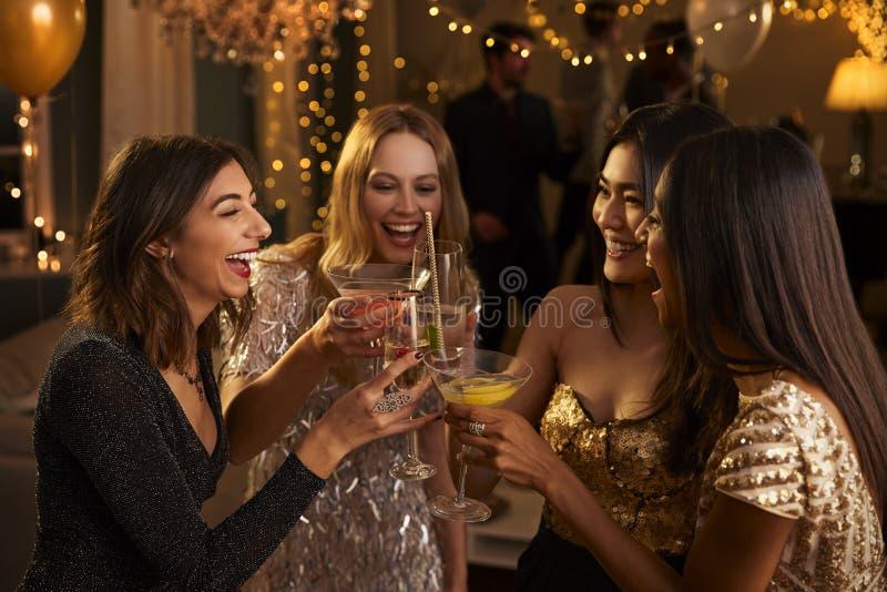 Los amigos femeninos hacen la tostada mientras que celebran en el partido foto de archivo