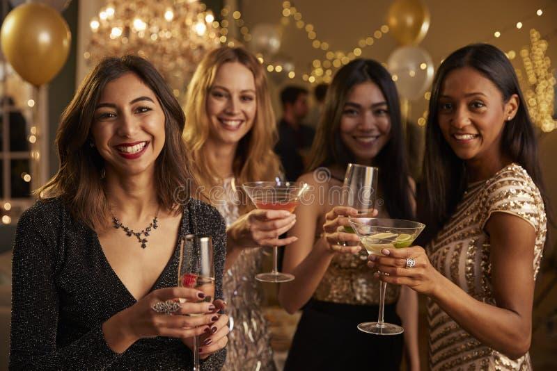 Los amigos femeninos que celebran en el partido hacen la tostada a la cámara imagen de archivo libre de regalías