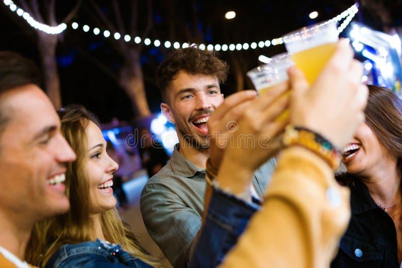Los amigos jovenes atractivos que tuestan con la cerveza adentro comen el mercado en la calle foto de archivo libre de regalías