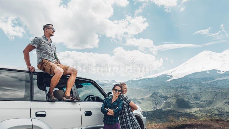 Los amigos jovenes de los viajeros disfrutan de la vista de montañas en verano fotografía de archivo