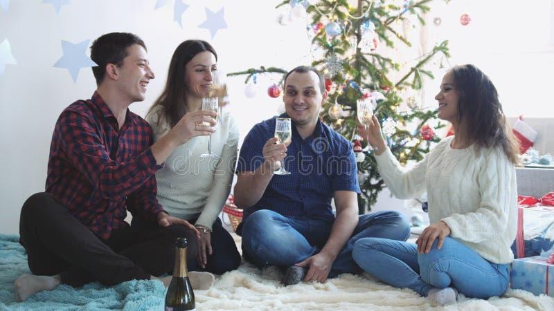 Los amigos jovenes felices beben el champán durante celebran Año Nuevo o Nochebuena, teniendo gran tiempo en hogar de relajación fotos de archivo libres de regalías