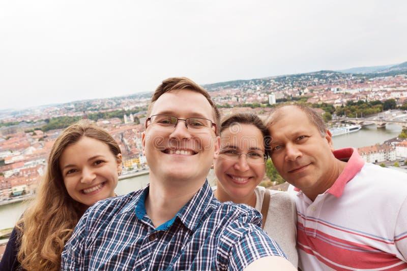 Los amigos jovenes felices toman una foto del selfie en un teléfono sobre una ciudad foto de archivo