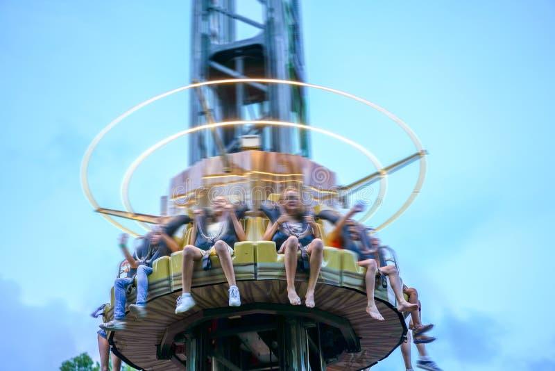 Los amigos jovenes se divierten en el parque Paseo feliz de los individuos en atracciones Parque del entretenimiento, diversión,  foto de archivo libre de regalías