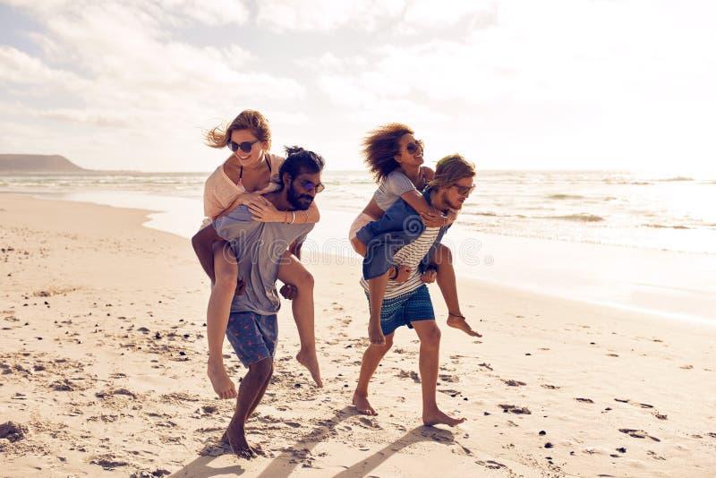 Los amigos llevan a cuestas a lo largo de la playa fotografía de archivo