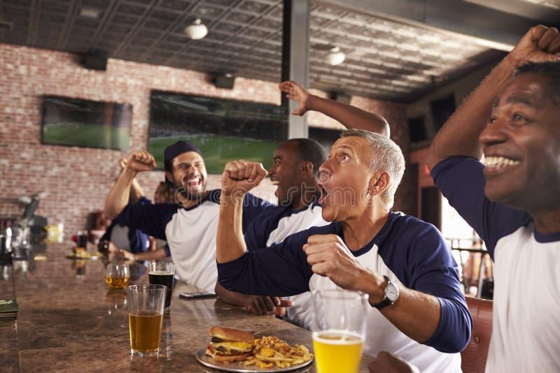Los amigos masculinos en juego del reloj de la barra de deportes y celebran imagen de archivo