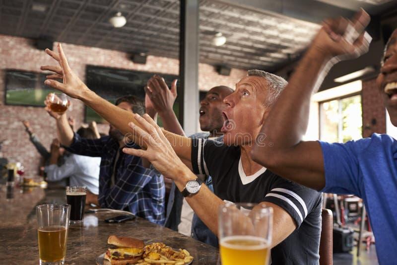 Los amigos masculinos en juego del reloj de la barra de deportes y celebran imagen de archivo libre de regalías