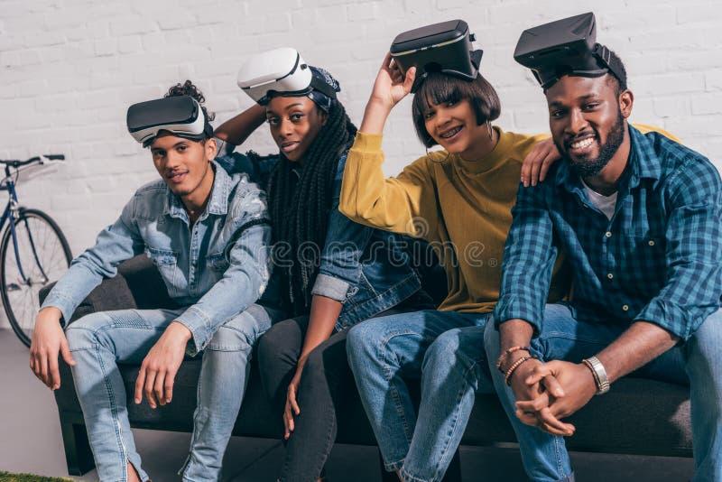 los amigos multiculturales jovenes con levantaron para arriba realidad virtual foto de archivo