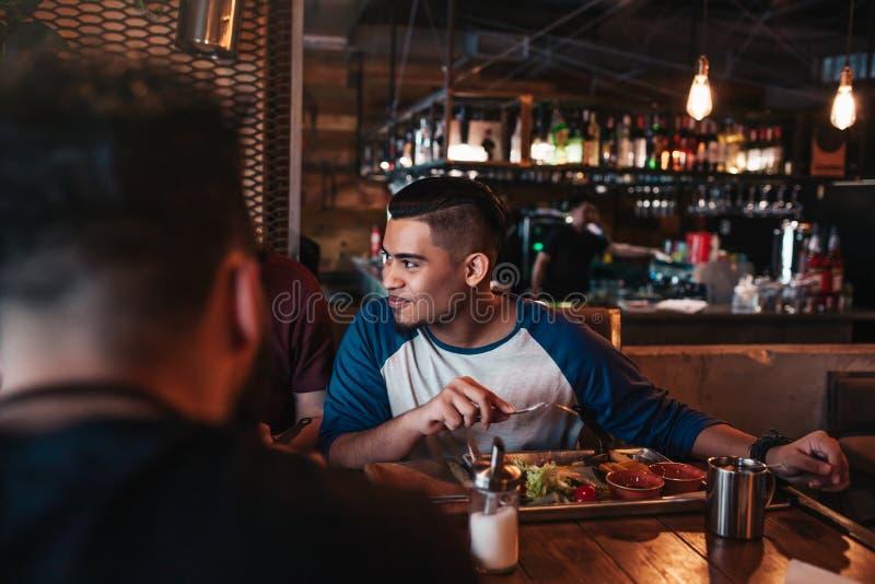Los amigos multirraciales comen el desayuno en barra del salón Los hombres jovenes charlan mientras que teniendo comida y bebidas imagenes de archivo