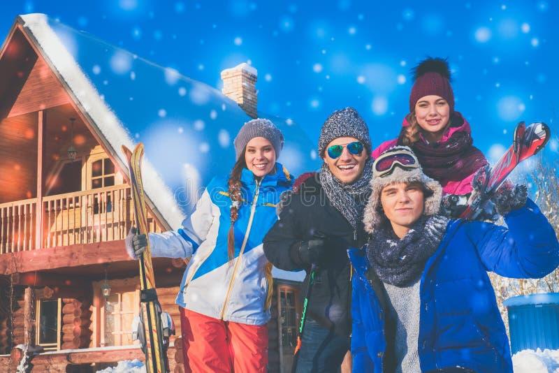 Los amigos pasan vacaciones de invierno en la cabaña de la montaña imágenes de archivo libres de regalías
