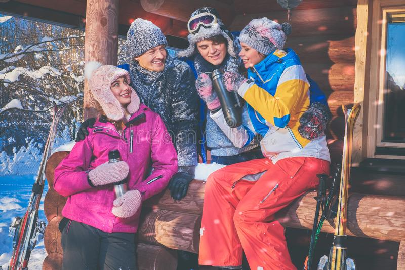Los amigos pasan vacaciones de invierno en la cabaña de la montaña fotos de archivo