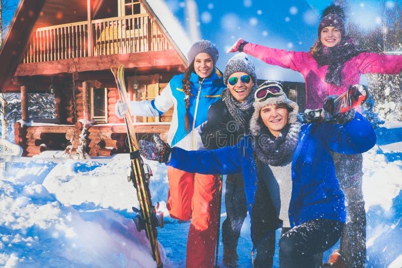 Los amigos pasan vacaciones de invierno en la cabaña de la montaña foto de archivo